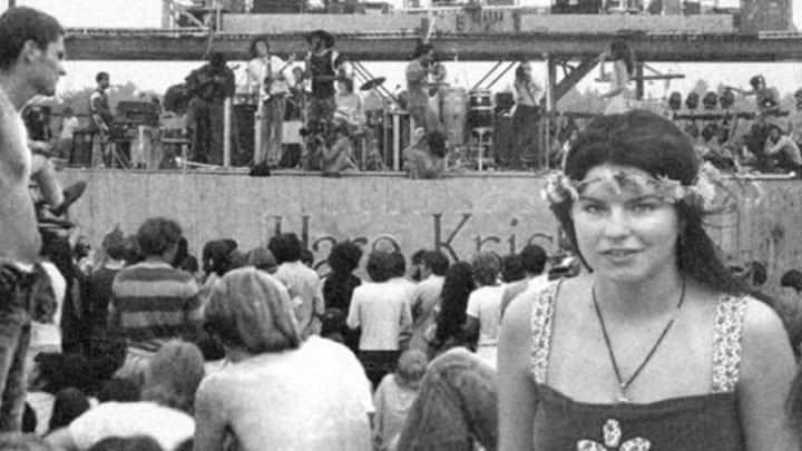 A Beautiful Woman Poses With The Woodstock Stage In The Background